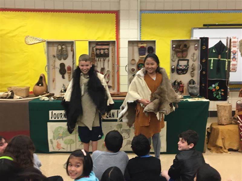 Two students wearing Native American clothing.