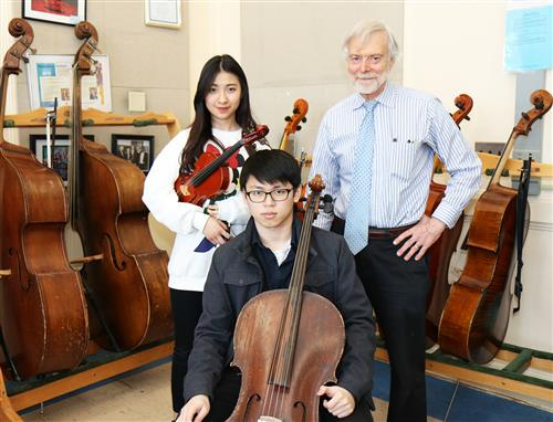 North High music teacher pictured with two student musicians
