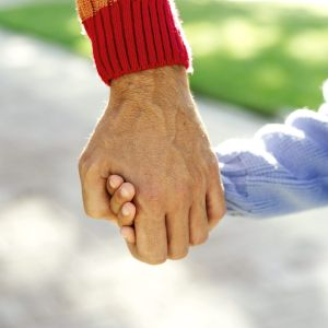 Photo of grown-up and child hand-holding close-up