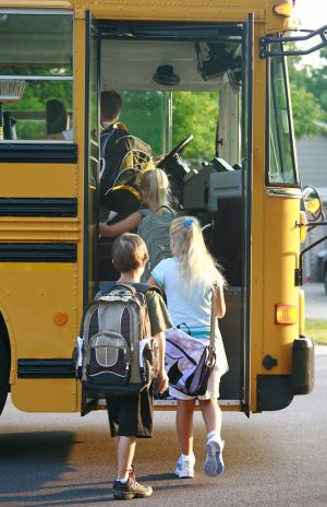 Photo of students with backpacks boarding school bus