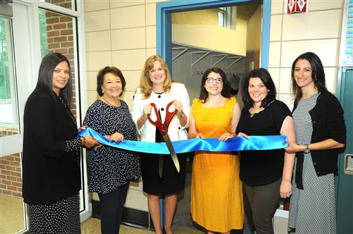 School administrators and social workers cut a ribbon to mark the grand opening.