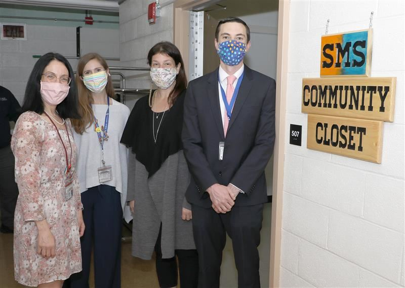 Two school administrators and two faculty members stand outside the South Middle Community Closet