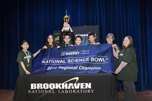 The winning team from South Middle is photographed with their trophy and banner.