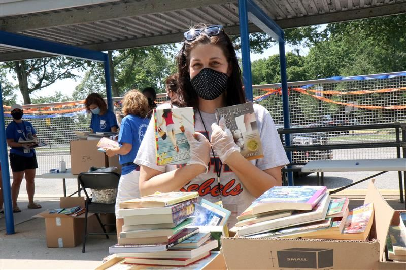 A teacher wearing a face mask and gloves holds up books during the Stop Drop and Read book drive