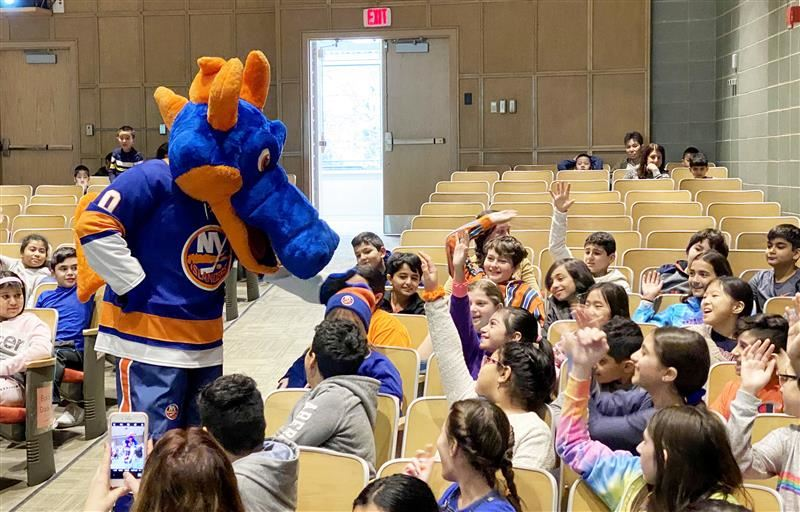 Sparky the Dragon, mascot for the NY Islanders, interacts with students in the audience