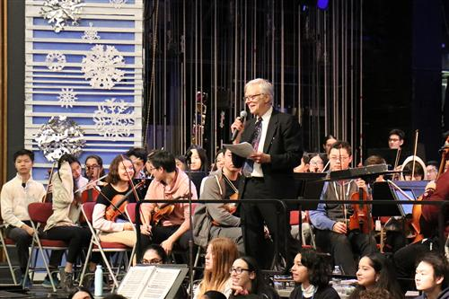 Joseph Rutkowski stands on stage, holding a microphone, with instrumental musicians seated behind him.