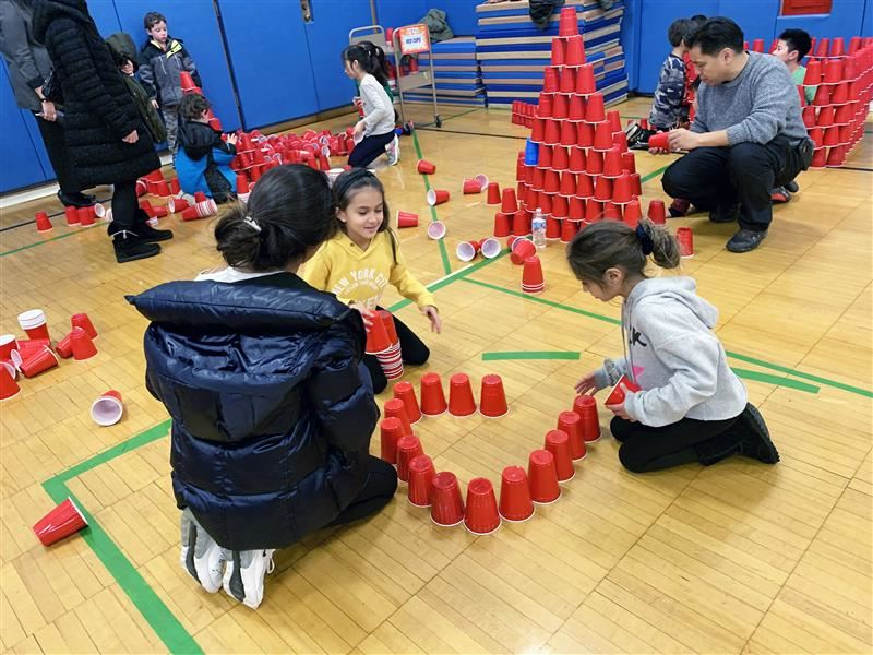 Adults and students build towers out of red solo cups during a STEM activity
