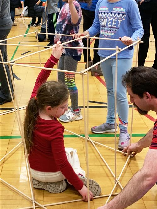 A father and daughter work together to build a structure out of wooden dowels.