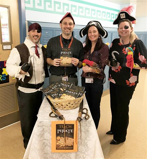 Staff dressed as pirates holding with books
