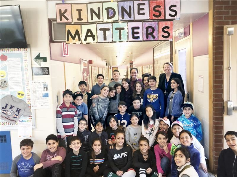 JFK Student Council members pose under a sign at the school that reads Kindness Matters