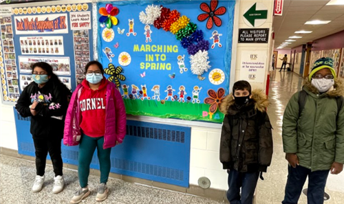 Four elementary students stand in front of a bulletin board with a colorful spring theme