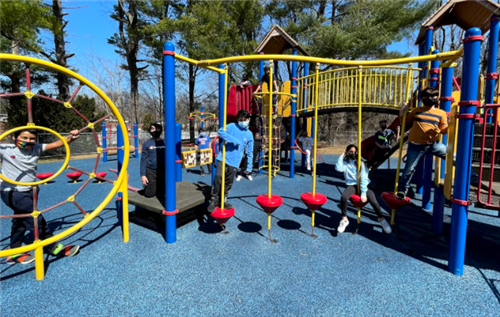 Four elementary students play outside on playground equipment on a beautiful spring day.