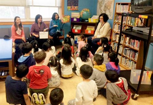An ENL teacher and the librarian read a book to students seated in the Lakeville School library.