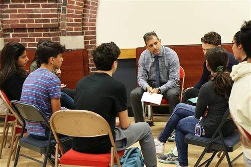 North High Principal Dr. Daniel Holtzman facilitates a small-group discussion with ninth graders following peer performances
