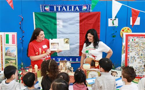 Two adults standing in front of the Italian flag speak to young students about Italian culture.
