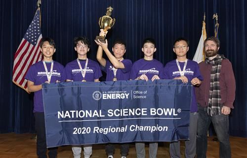 A five-member team of students hold a trophy on stage accompanied by their team coach