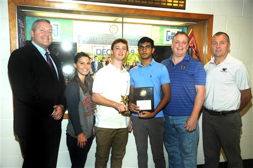 Two award-winning South High students are congratulated by the school principal and faculty members
