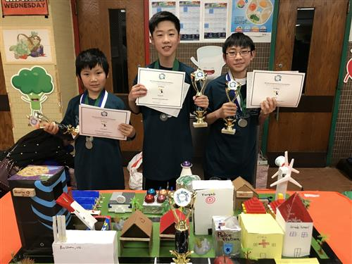 Three South Middle students pose with their trophies from the Future Cities Competition
