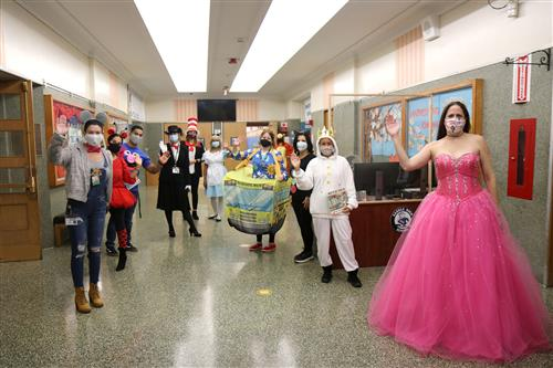 Saddle Rock staff members stand in the school's main lobby, dressed as book characters, to greet students.