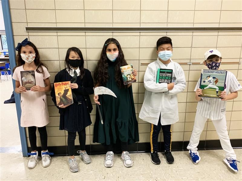 Five students are dressed in costumes based on book characters