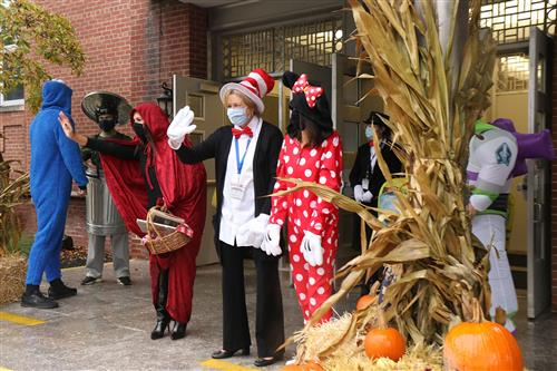 The Superintendent, Principal, and Assistant Principal, dressed in costumes, welcome students during arrival time.