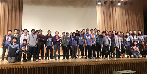 Great Neck high school students wearing medals and holding a trophy at the Science Olympiads