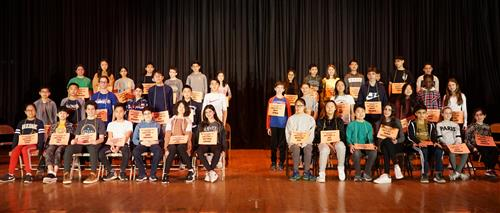 Forty-two spelling bee contestants on stage at North Middle School