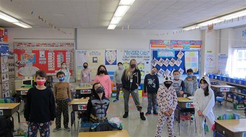 A class of students stand at their socially distanced desks while wearing pajamas on a pajama-themed spirit day