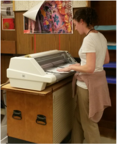 Photo of Teacher Using Laminating Machine