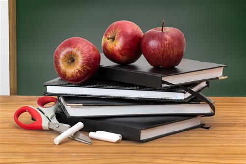 Picture of school books with chalk and apple