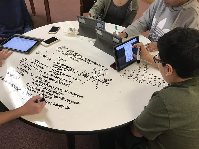 Students work on math problems using the library's whiteboard table