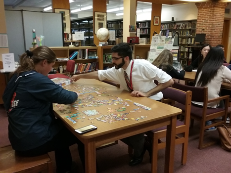 Mr. Miata and students work on puzzles in the library